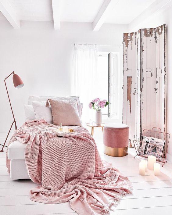 une chambre blanche accueillante avec un pouf rose, une literie rose et blanche, une lampe rose et un porte-revues est wow