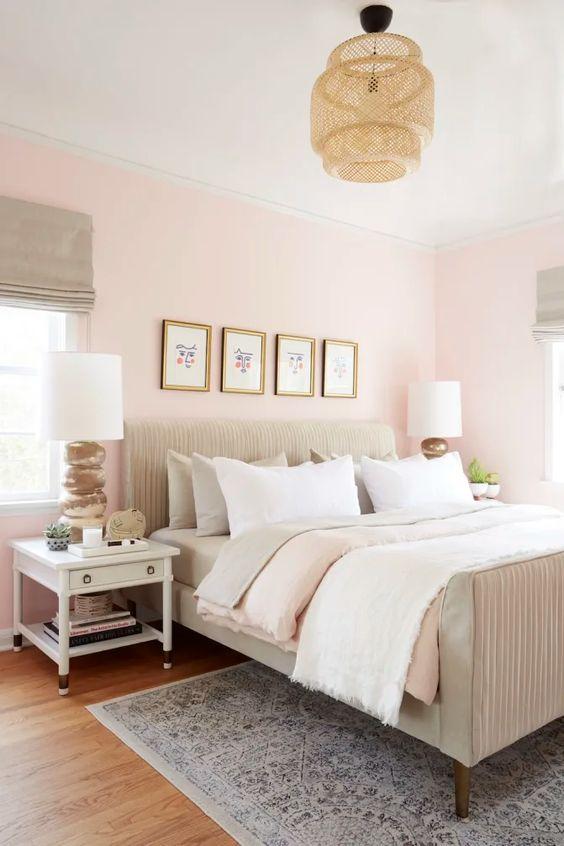 une chambre moderne et accueillante avec des murs rose clair, un lit neutre, une lampe en osier et des meubles blancs et un mur de galerie