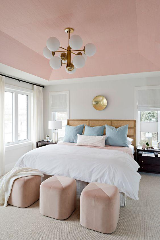 une chambre moderne et élégante avec un plafond rose et des poufs en blocs de couleur, des oreillers bleus et des touches d'or