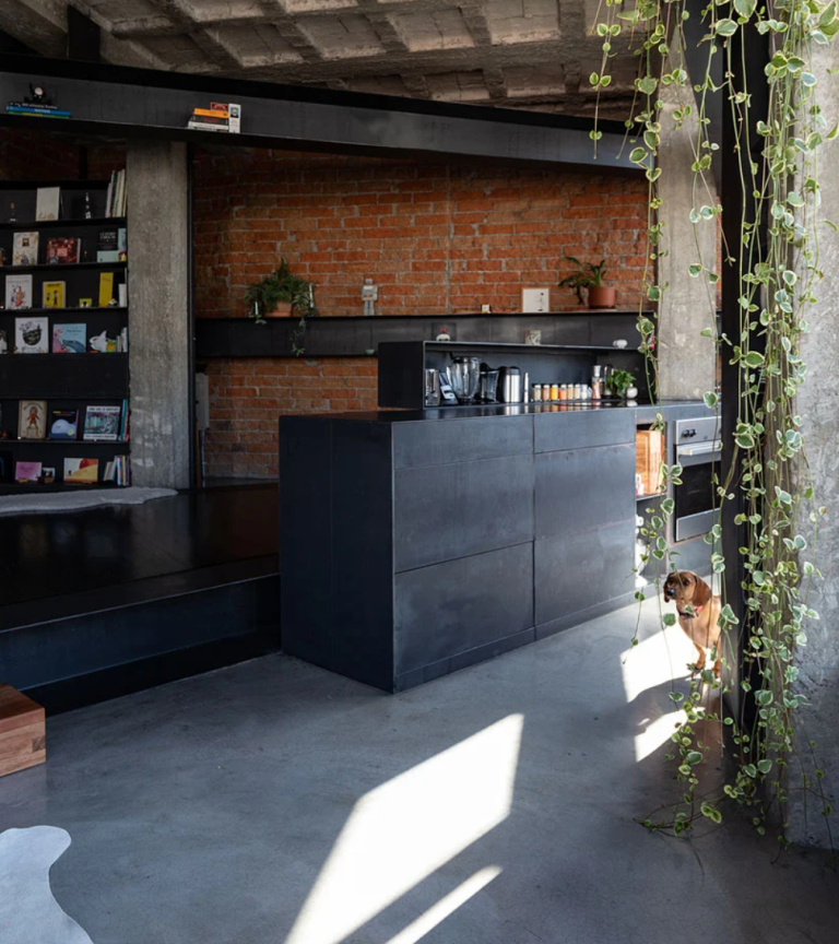Le mobilier est en métal foncé, il y a des murs en briques et quelques touches de bois pour adoucir le look