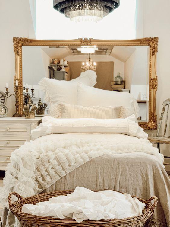 un magnifique miroir de déclaration dans un cadre doré raffiné est une belle alternative à une tête de lit qui agrandira l'espace