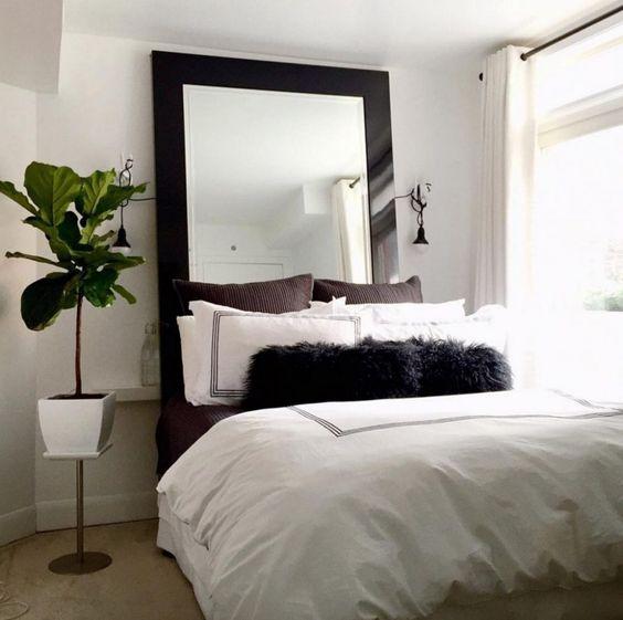 une petite chambre neutre avec un miroir moderne dans un cadre sombre qui attire l'attention et rend l'espace cool