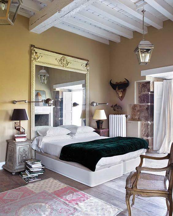 une chambre éclectique avec un miroir surdimensionné dans un cadre vintage et des meubles shabby chic qui rendent l'espace raffiné