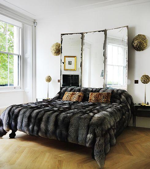 une chambre luxueuse moderne avec un miroir vintage comme tête de lit, un couvre-lit en fausse fourrure et quelques touches d'or
