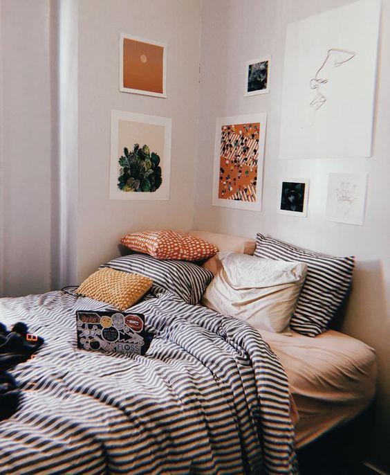 un mur de galerie joli et lumineux qui pend au-dessus du lit au lieu d'une tête de lit et continue jusqu'au mur suivant