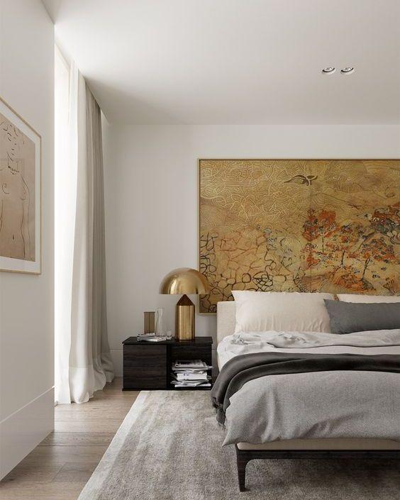 une chambre chic et élégante avec une œuvre d'art et des lampes en laiton audacieuses qui ajoutent du chic et un look cool à l'espace