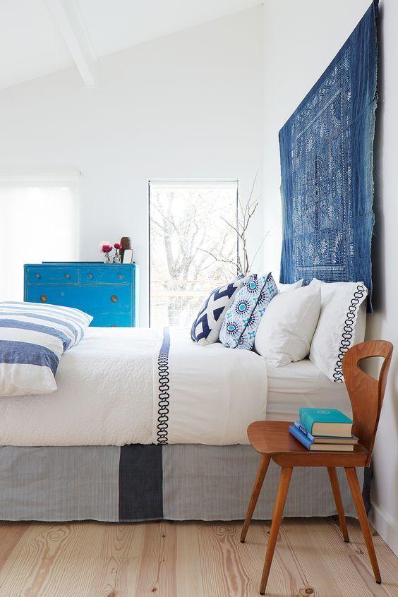 une chambre audacieuse et vivante en blanc, avec des textiles imprimés et colorés, une tapisserie bleue au lieu d'une tête de lit habituelle