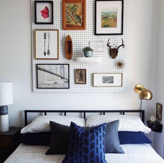 un panneau perforé blanc avec des œuvres d'art et de la verdure en pot sur le lit est une alternative créative et cool à une tête de lit habituelle