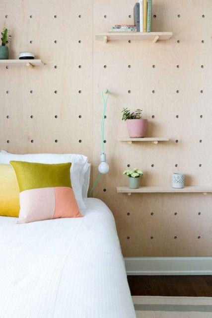un mur en panneaux perforés avec diverses étagères, des fleurs en pot et de la verdure et même une ampoule attachée pour plus de fonctionnalité