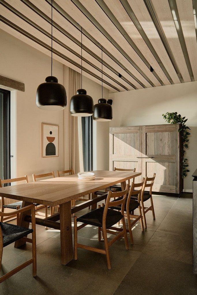 Ceci est un espace salle à manger intérieur avec des lampes noires fraîches, des chaises noires, des meubles en bois et des chaises noires