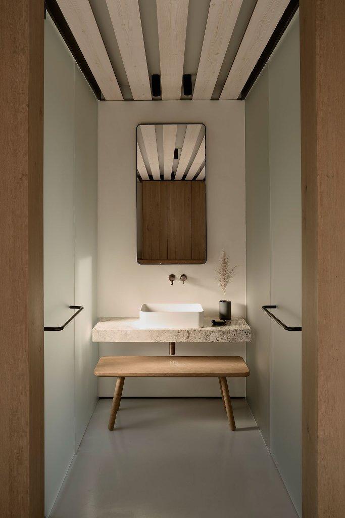 La salle de bain est minimaliste, avec une vanité en pierre, un banc en bois et des douches en verre dépoli