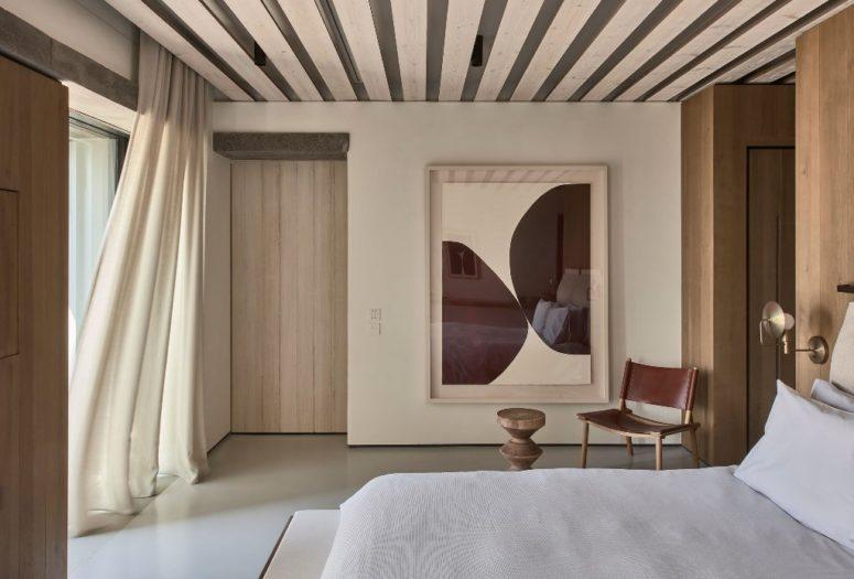 La chambre principale présente des panneaux de bois, un lit confortable, des appliques et une œuvre d'art remarquable