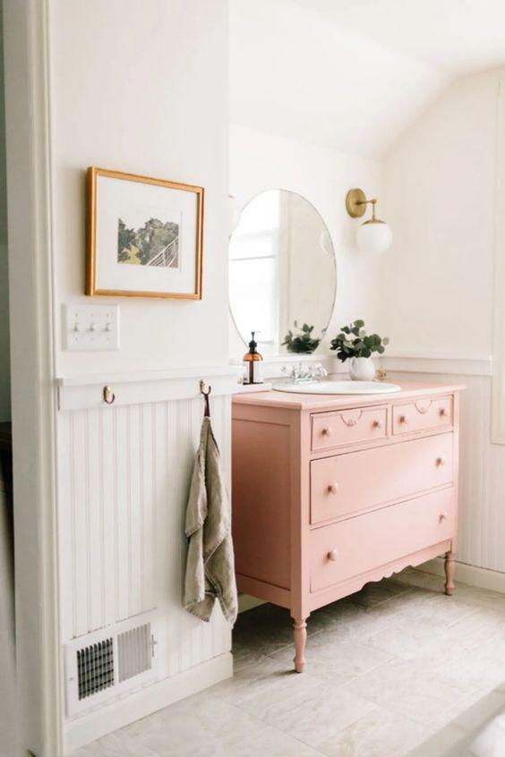 une salle de bain chic et mignonne avec un panneau de perles blanc, une coiffeuse rose, un miroir rond, de la verdure en pot et des appliques est éthérée
