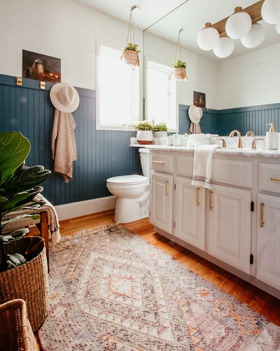 une salle de bain bohème chic avec un panneau de perles bleu, une grande vanité et un mur de miroir, des plantes en pot et des tapis en couches