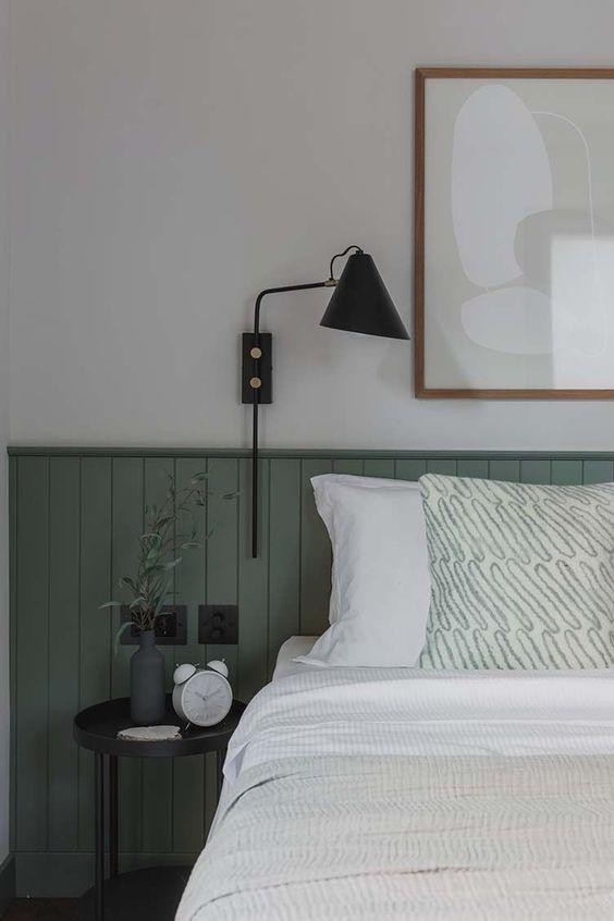 une chambre chic avec des panneaux de perles verts, une table de chevet et une applique noire, une œuvre d'art neutre et quelques accessoires