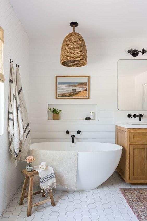 une salle de bain de plage chic faite avec un mur de perles blanches, des carreaux hexagonaux, une lampe en osier et une vanité en bois plus des touches de noir