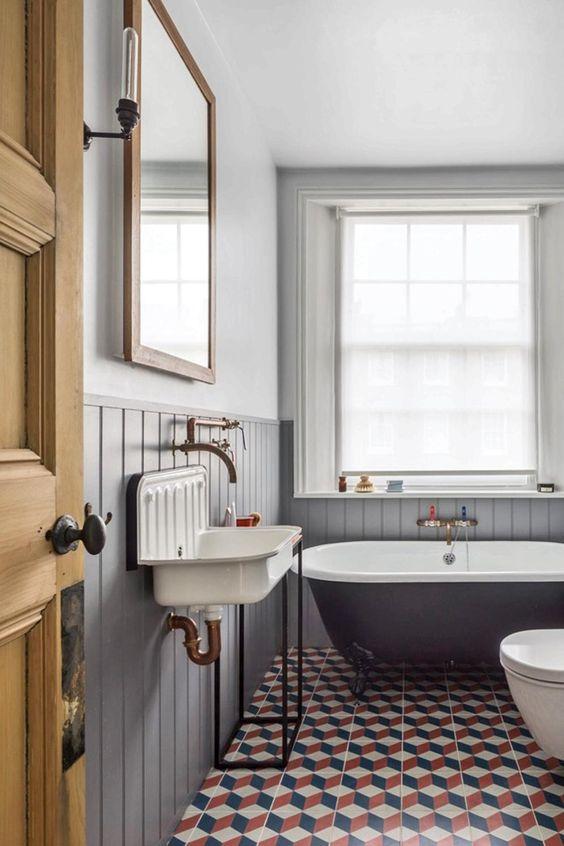une salle de bain chic inspirée du vintage, avec des panneaux de perles gris, une baignoire noire, un lavabo vintage et une grande fenêtre avec des stores