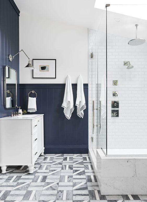 une salle de bain contrastée avec des carreaux blancs, des panneaux de perles bleu marine, une lucarne et des carreaux imprimés au sol plus une vanité blanche