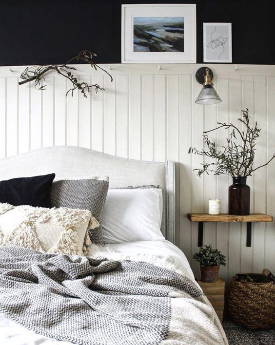 une chambre contrastée avec des murs noirs, des panneaux de perles blancs, un lit rembourré, des touches et des branches en bois et en osier