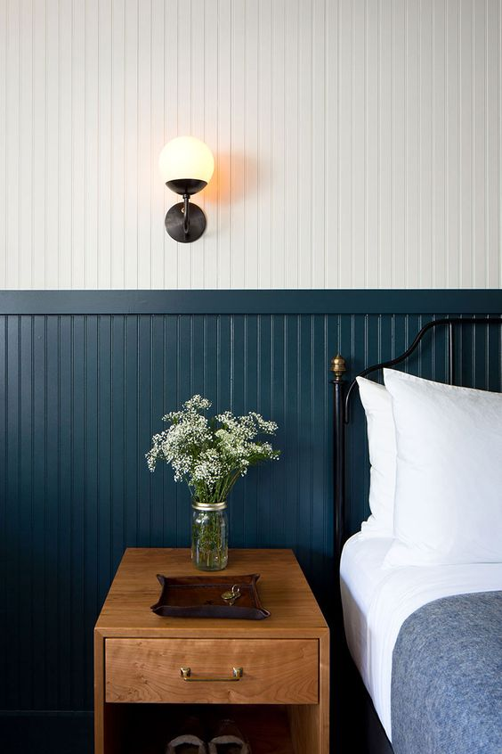 une chambre chic d'inspiration vintage avec des panneaux de perles blancs et bleu marine recouvrant entièrement le mur, un lit forgé noir et une table de chevet en bois
