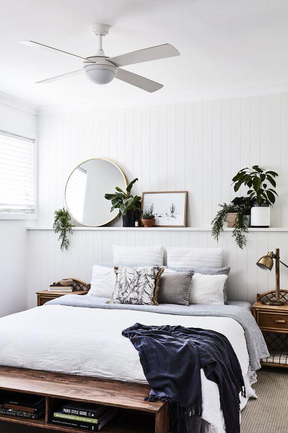 une chambre côtière chic avec un mur en lambris blanc, des meubles en bois, des plantes en pot et de la verdure, un miroir rond et des textiles confortables