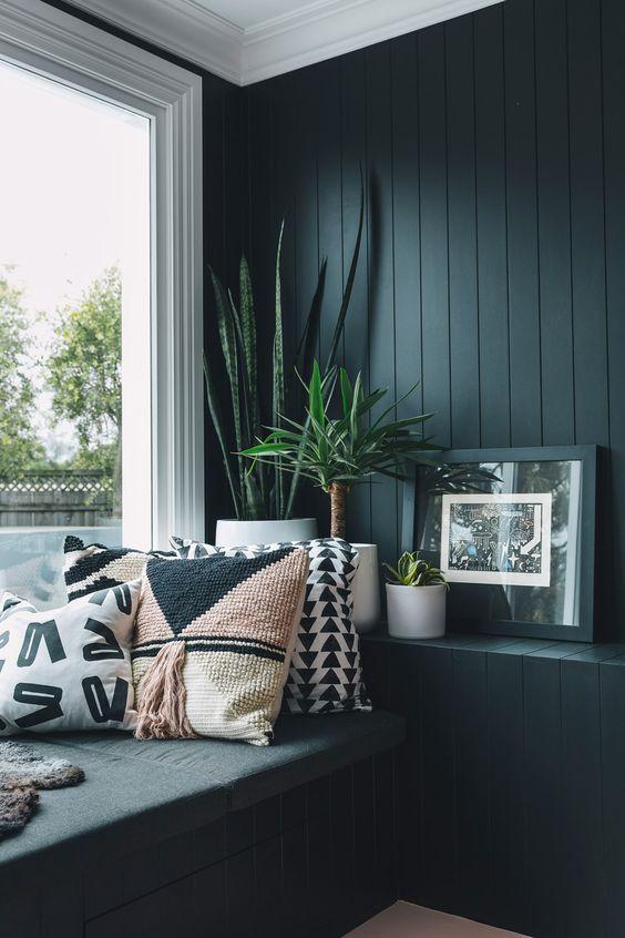 un coin de fenêtre confortable avec un mur de panneaux de perles noirs, un lit de repos au bord de la fenêtre et une grande fenêtre ainsi que des plantes en pot