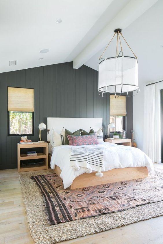 une chambre de ferme moderne avec un mur en placoplâtre noir, des meubles tachés de lumière, beaucoup de lumière naturelle et des tapis en couches