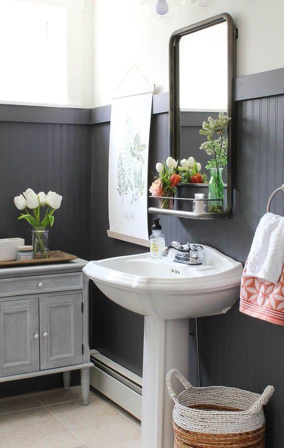 une salle de bain de ferme avec des panneaux de perles noirs, des meubles vintage, un lavabo sur pied et des fleurs et de la verdure