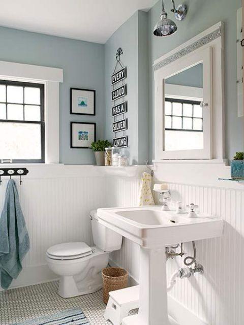 une salle de bains de ferme vintage confortable avec des murs bleu clair, des panneaux de perles blancs, un lavabo sur pied, de l'art et beaucoup de lumière