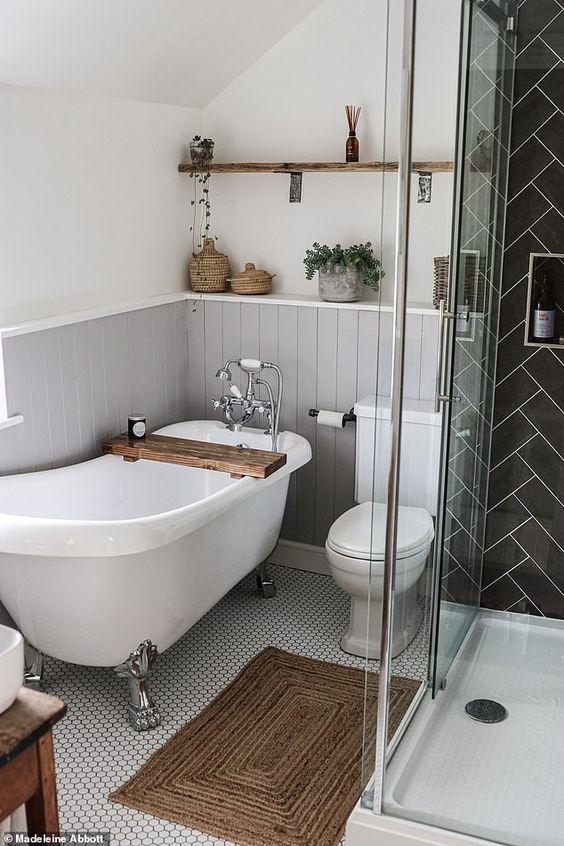 une petite salle de bain mignonne avec des panneaux de perles gris, un espace douche en carrelage noir, du carrelage en bois et de la verdure en pot