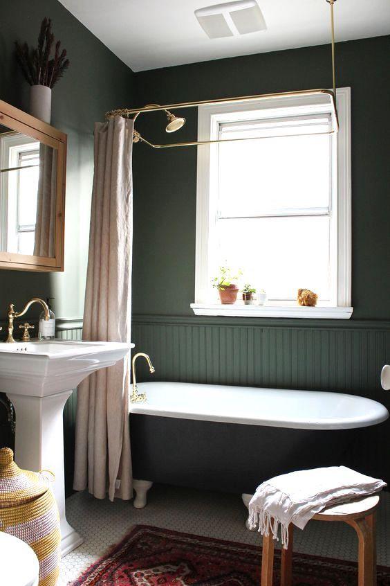 une salle de bains sombre d'inspiration vintage avec des murs et des panneaux de perles vert chasseur, une baignoire noire, un sol carrelé et un lavabo sur pied ainsi que des touches de laiton