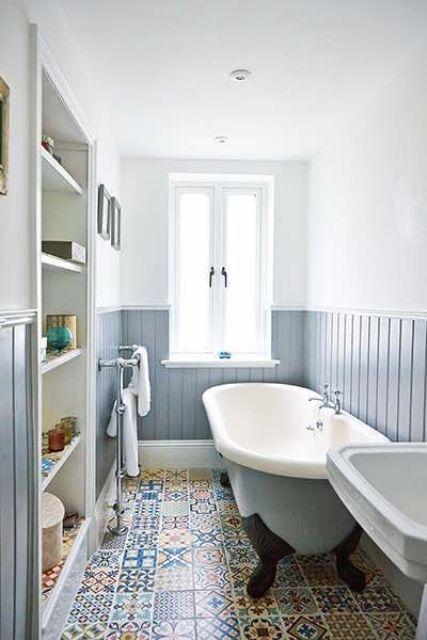 une salle de bain neutre et accueillante avec un panneau de perles bleu poudré, des carreaux imprimés, un meuble de rangement intégré et une baignoire bleue