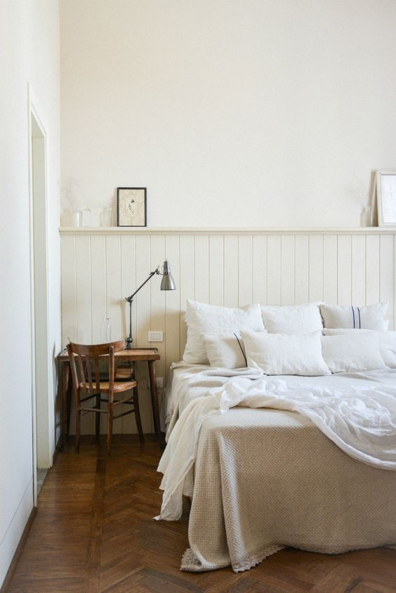 une chambre neutre avec des panneaux de perles neutres, un bureau et une chaise en bois, quelques touches vintage ici et là