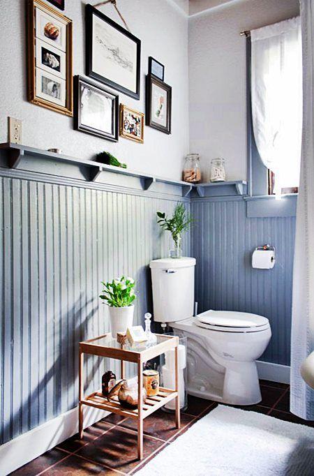 une petite salle d'eau avec un panneau de perles bleu poudre, une fenêtre, un mur de galerie et des carreaux sombres au sol