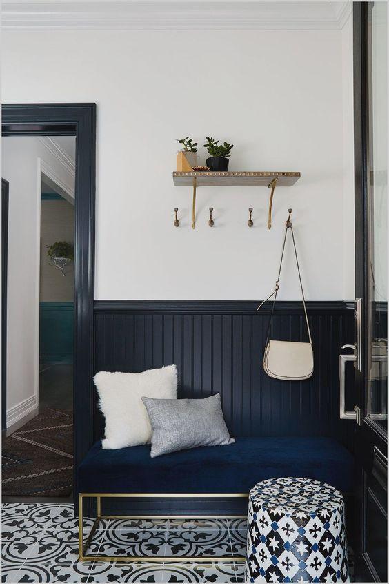 une entrée élégante avec un panneau de perles bleu nuit, un banc bleu marine, des carreaux imprimés sur le sol et un pouf imprimé lumineux