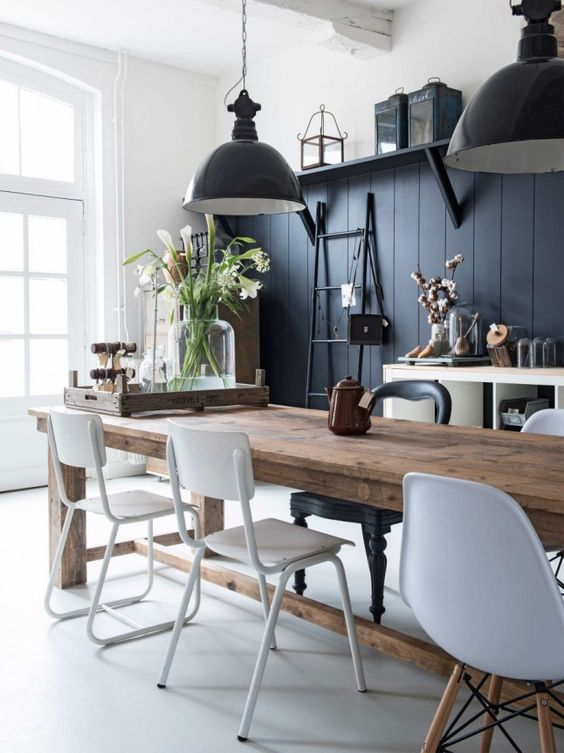 une salle à manger vintage avec un mur de perles noires, des suspensions noires, une table en bois et des chaises blanches a l'air chic