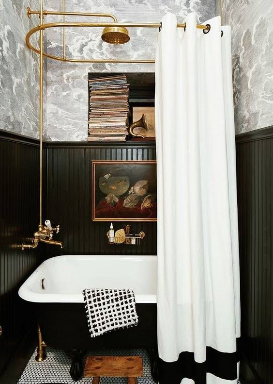 une salle de bain d'inspiration vintage avec du papier peint et des panneaux de perles noirs, une baignoire noire, des livres et des œuvres d'art vintage