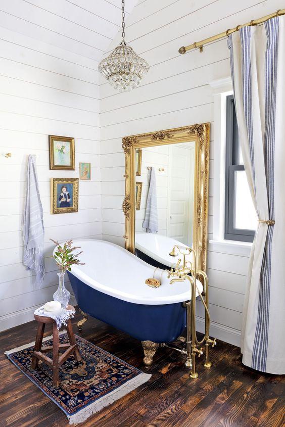 une salle de bain éclectique revêtue de panneaux de perles blancs, avec une baignoire bleu marine, un miroir de déclaration, un lustre en cristal et un mur de galerie