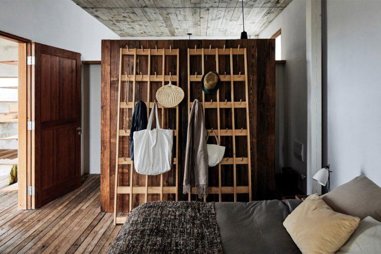La chambre principale présente un grand placard en bois et un lit confortable avec beaucoup d'oreillers