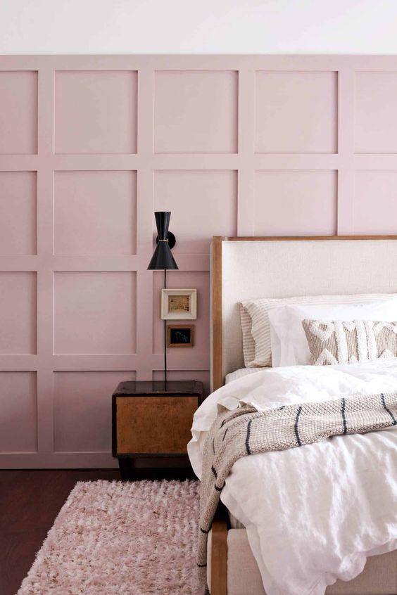une chambre chic avec un mur lambrissé rose, un lit blanc, des tables de nuit et des appliques foncées ainsi qu'une literie brodée neutre