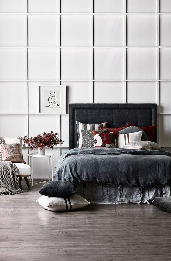 une chambre contrastante avec un mur lambrissé blanc, un lit rembourré blakc, une literie sombre et une chaise blanche est ultra-moderne