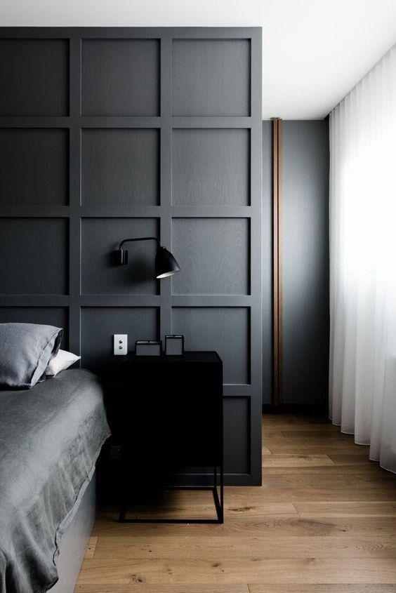 une chambre à coucher contemporaine avec un mur lambrissé gris graphite qui sépare l'espace de couchage du placard