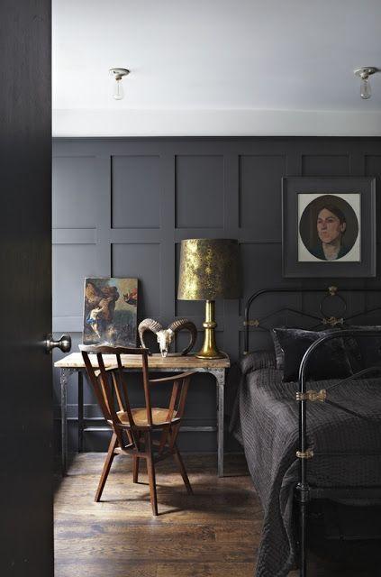 une chambre de mauvaise humeur avec un élégant mur lambrissé gris anthracite, un lit en métal noir et une décoration et des œuvres d'art vintage