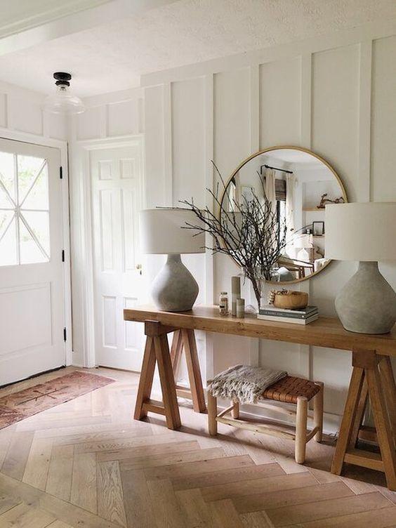 une entrée de ferme avec des murs lambrissés blancs, des meubles en bois, des lampes chics et beaucoup de lumière naturelle