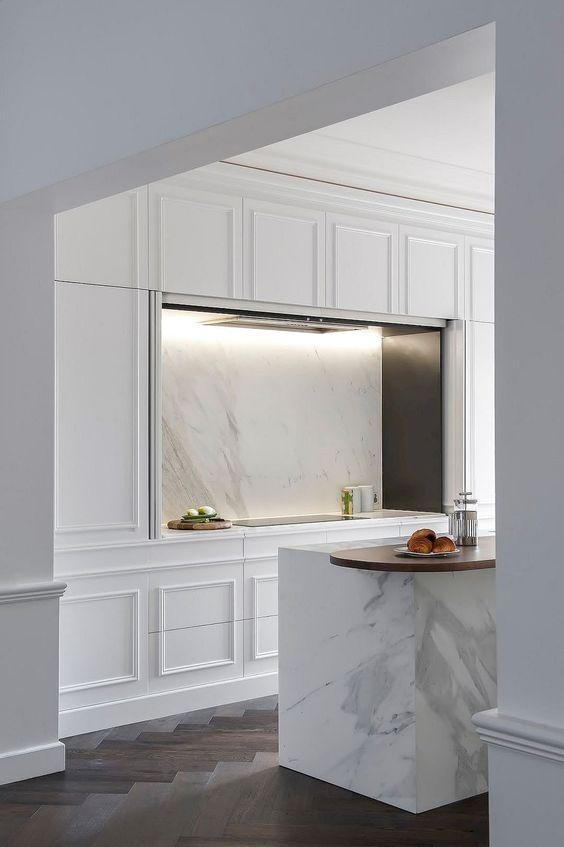une cuisine blanche moderne et élégante avec des lambris partout, des appareils encastrés et un dosseret en marbre blanc