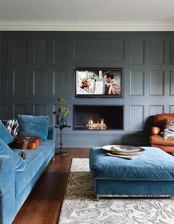 un salon luxueux et moderne avec des murs lambrissés gris, des meubles bleus et une cheminée intégrée et une télévision