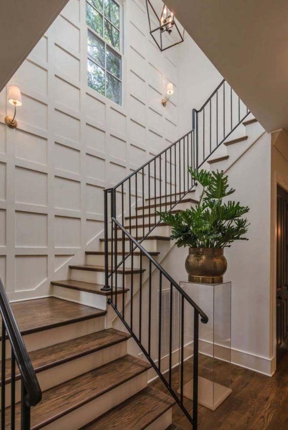 une entrée élégante avec un mur lambrissé blanc qui semble accrocheur et non ennuyeux comme le font de nombreux autres murs neutres