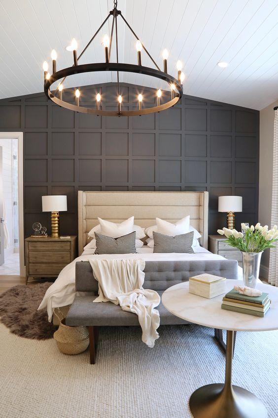 une chambre élégante avec un mur lambrissé noir, un lit et un banc rembourrés, un lustre rond, des tables de chevet en bois et des tapis en couches