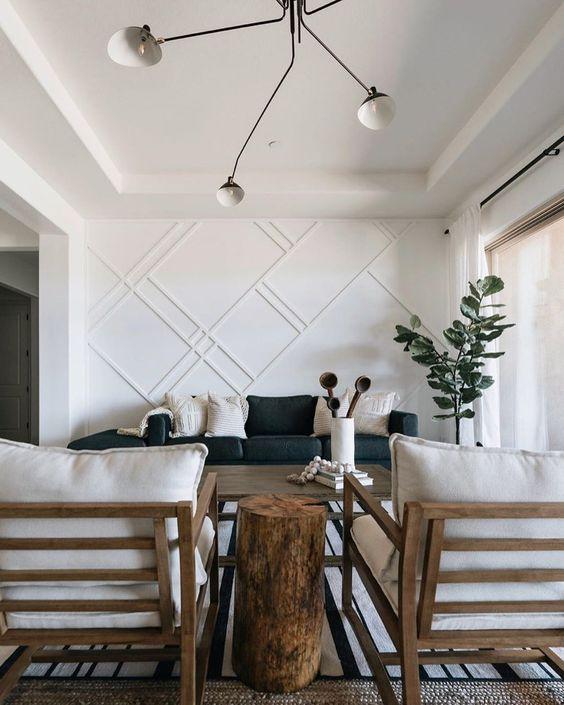 un salon élégant avec un mur lambrissé blanc qui fait un accent et semble audacieux ajoutant du style et du chic à l'espace