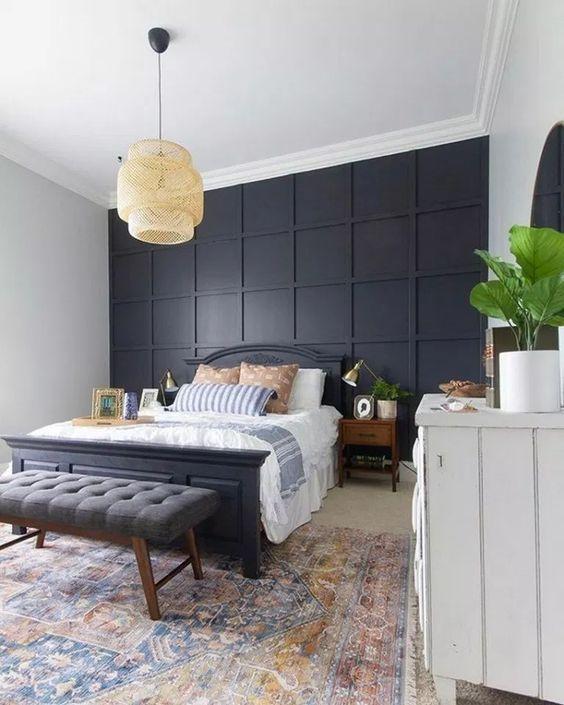 une chambre élégante dans des styles modernes et bohèmes, avec un mur lambrissé noir, un lit noir et un banc gris plus une lampe en osier